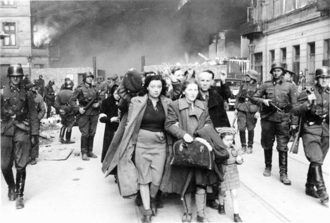 Warsaw Ghetto burning: Captured Jews in the Warsaw Ghetto are led by German soldiers to deportation.  The woman on the left at the head of the column is holding onto the right arm of her mother-in-law, and her child is in tow.  The child's father can be seen to the girl's left.  Of the four, only he survived the war.