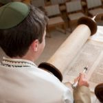 Young man reading from the Torah scroll