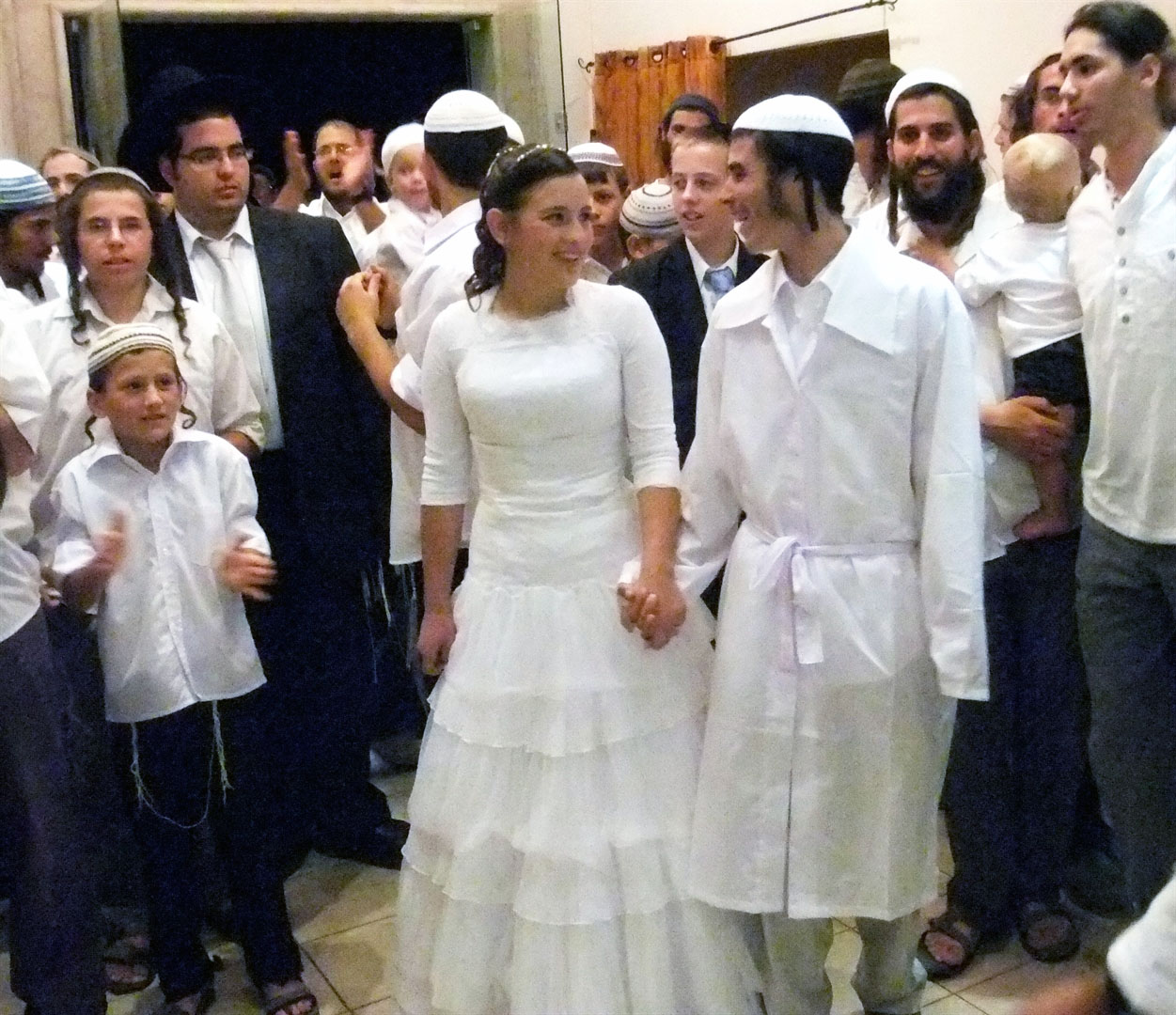 An Orthodox Jewish wedding in Jerusalem: Traditionally, on the day of his wedding, the chatan (groom) wears first wears the kittel (white linen garment), which signifies purity, holiness and new beginnings.  Thereafter, he wears it on special occasions such as Rosh Hashanah (New Year's), Yom Kippur (Day of Atonement), and Pesach (Passover).
