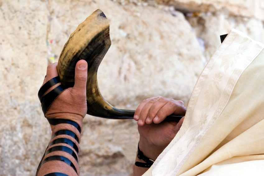 Jewish man sounding the shofar on Rosh Hashanah at the Western (Wailing) Wall in Jerusalem.