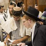 Young-Jewish-men-read-Torah-scrolls-Western-Wall-Jerusalem