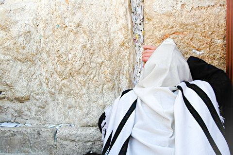 A Jewish man prays at the Western (Wailing) Wall with his tallit (prayer shawl) over his head.