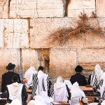 Jewish men pray at the Western Wall Plaza in Jerusalem