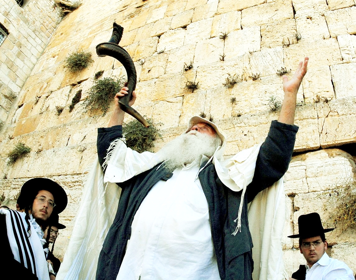 A Jewish man praises God at the Western (Wailing) Wall in Jerusalem.  In his hand is a Yemenite-style shofar, which is blown during the High Holy Days.  <em>(Psalm 98:6)</em>
