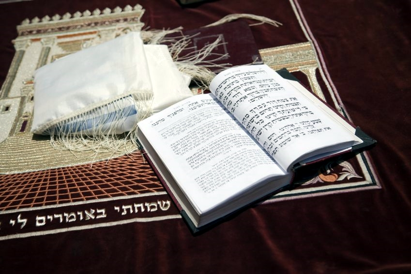 This Siddur (Jewish Prayer Book) is resting on a table at the Western Wall adorned with a velvet tablecloth that is embroidered with an image of the Second Temple.