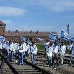 A visitor to Auschwitz carries the Israeli flag as a group examines a boxcar used to transport Jews to extermination and concentration camps.