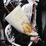 """It is traditional to hold the Torah with the right arm and rest it on the right shoulder since Deuteronomy 33:2 states, """"From his right hand went a fiery law for them."""""""