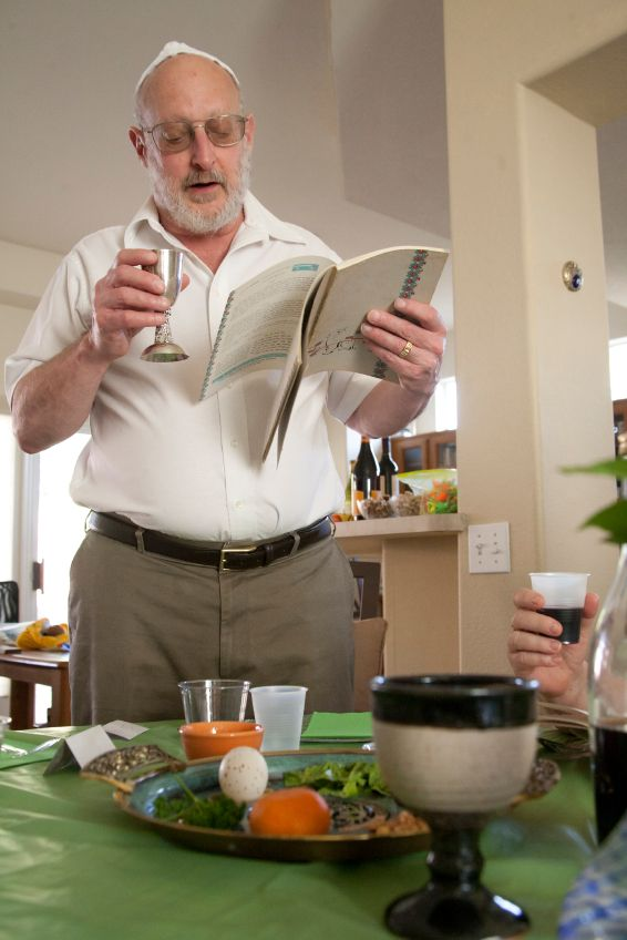 A Jewish man reads from the Haggadah during the Seder reciting the blessing over one of the Four Cups associated with redemption.
