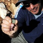 IAA archaeologist Pablo Betzer holds up a Jewish Revolt coin found outside Jerusalem