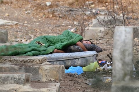 A homeless person in Israel sleeps in a cemetery on a mattress.  The month of Elul is a time to go out of our way to help the poor and needy.