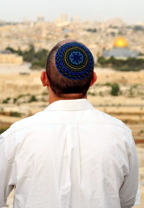 A Jewish man stands on the Mount of Olives facing the Temple Mount in Jerusalem.