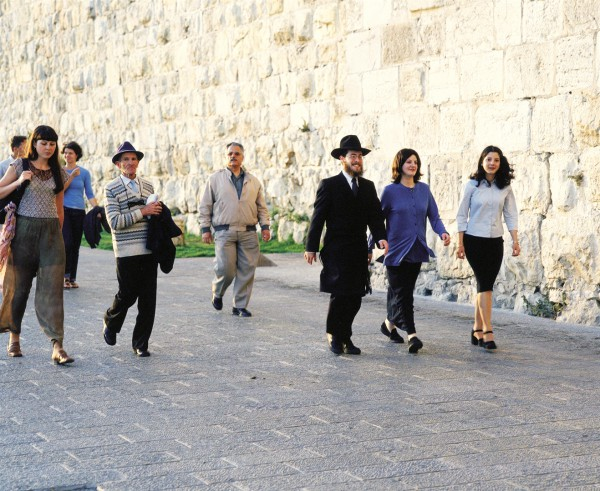 People walk along the walls of the Old City of Jerusalem. (Photo: Go Israel)