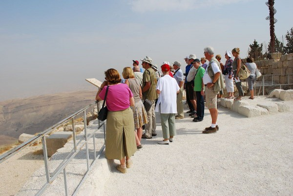 Pilgrims and tourists consider the view from Mount Nebo.