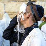 A Jewish man wearing tefillin (phylacteries) recites selichot (prayer for forgiveness and mercy) at the Western (Wailing) Wall during the Days of Awe.