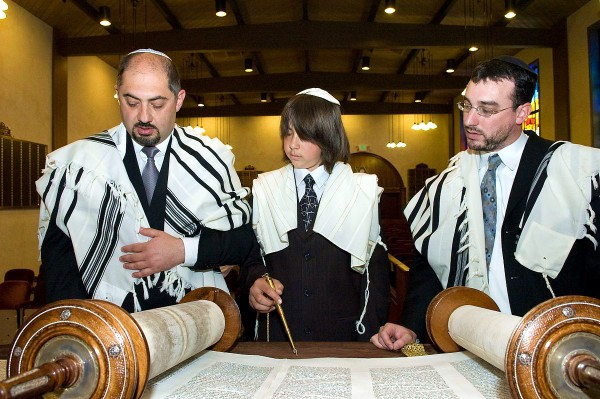 A 13-year-old Jewish boy reads from the Torah publicly for the first time.