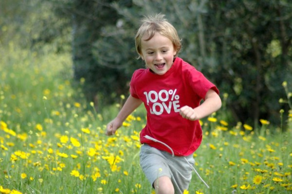 An Israeli lad runs through a meadow.