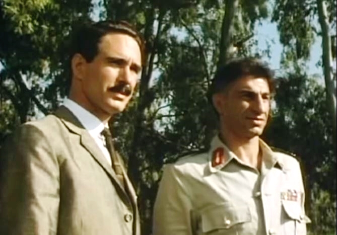 John Shea portrays Eli Cohen in The Impossible Spy.  In this scene, he is with a Syrian generalon the Golan Heights looking toward Israel during a trip to survey Syrian fortifications.  (YouTube capture)