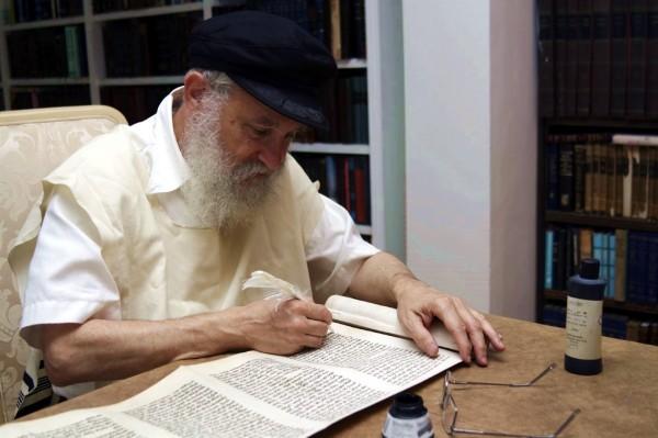 A Jewish scribe handwrites a Torah scroll.