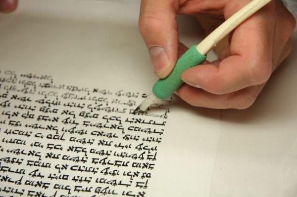 A Jewish scribe completes a Sefer Torah (Torah scroll).