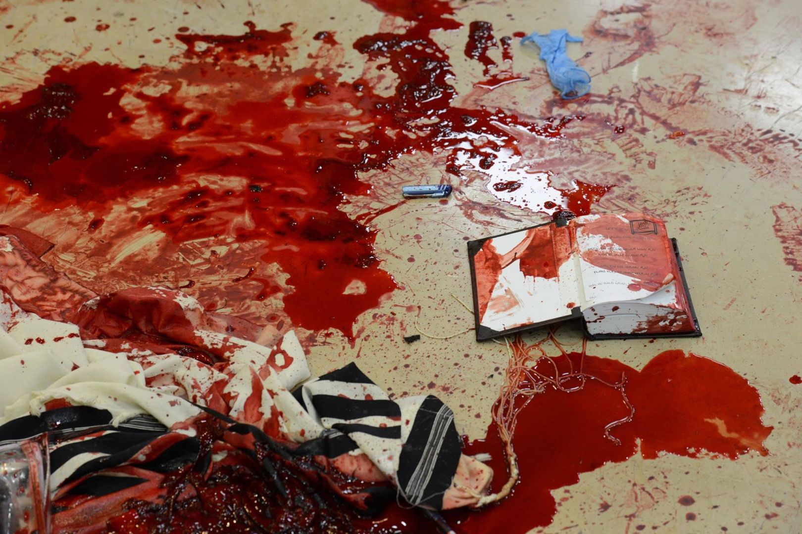The blood of victims mingled with a tallit (prayer shawl) and a siddur (Jewish prayer book) in the floor of Kehillat Bnei Torah synagogue in Jerusalem.  (Photo: GPO)