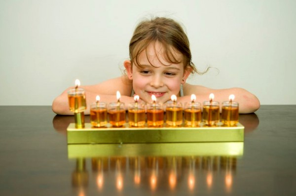 Fully lit oil hanukkiah with the shamash raised at the end.