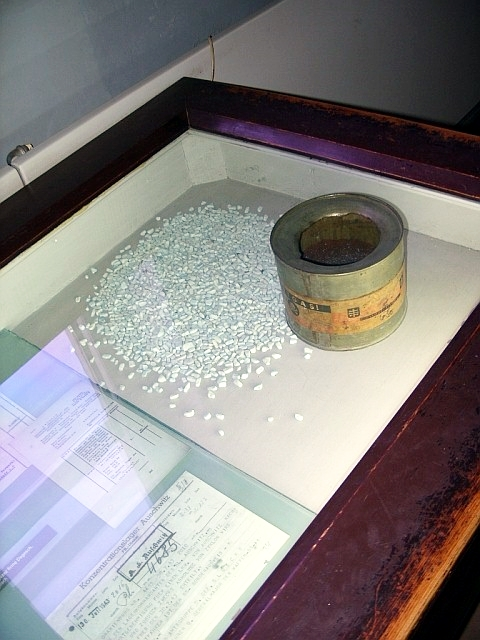 """A can of Zyklon B with adsorbent granules and original signed documents detailing ordering of Zyklon B as """"materials for Jewish resettlement"""" are on display at the Auschwitz concentration camp museum."""