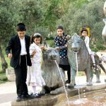Orthodox siblings play at the Lions Fountain in Jerusalem