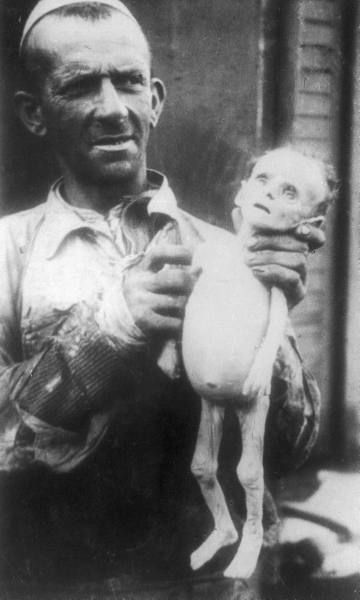 A man holds a Jewish infant who starved to death in Poland's Warsaw Ghetto. Photos such as this served to record the horrors of ghetto life for posterity.