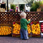 A child selects fruit at an outdoor market in Tel Aviv.