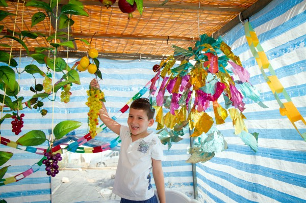 An Israeli boy helps to decorate the Sukkah during Sukkot (Feast of Tabernacles). (Go Israel photo by Dana Friedlander)