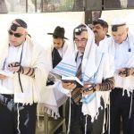 Jewish men wearing tallitot pray at the Western (Wailing) Wall in Jerusalem.