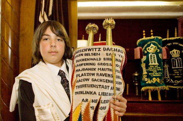 A Jewish teen holds a Torah scroll covered by an ornately decorated Torah mantle that commemorates those who perished in Nazi death camps during the Holocaust.
