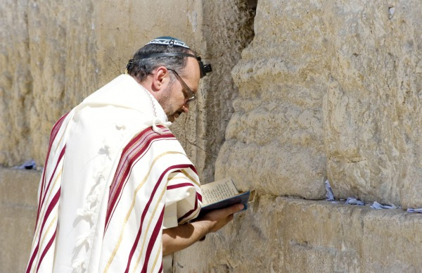 A Jewish man recites morning prayer (Shakharit) in Jerusalem at the Western Wall.