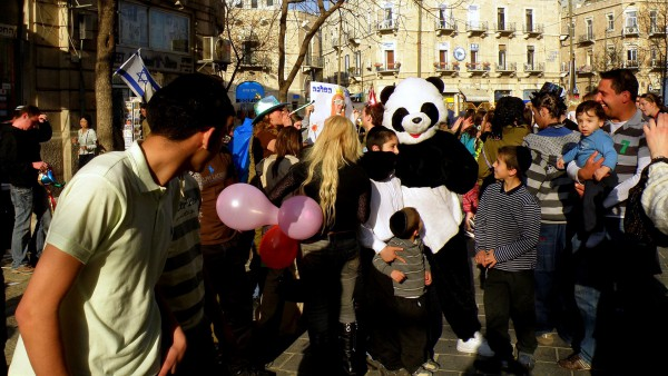 Purim is a joyous festival of costumes, parades and parties.  In the above   photo, Israelis celebrate Purim in the streets in Jerusalem.  (Photo by   Ron Almog)