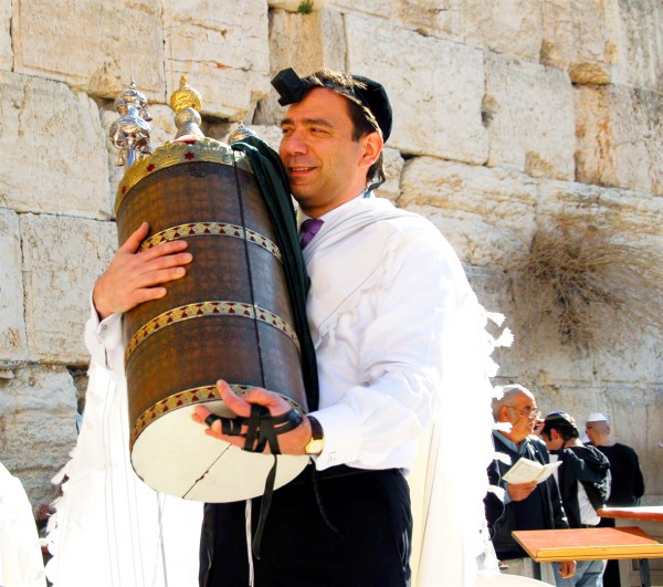 A Jewish man wearing tefillin (phylacteries) holds a Torah scroll protected by a study case called a tik.