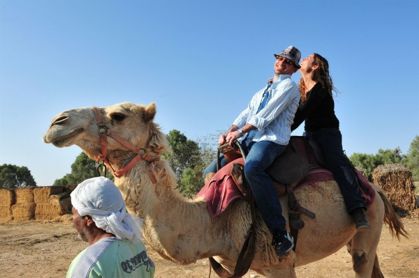 A husband and wife enjoy a camel ride together in Israel's Negev Desert.