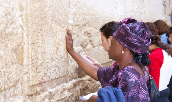 A woman touches the Wall as she prays in Jerusalem.