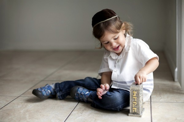 A Jewish boy puts money in the pushke, a box kept in Jewish homes for collecting funds to give to the poor and other benevolence.