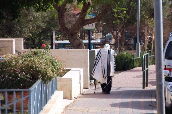A Jewish man walks home from morning prayers in Israel. (Flickr photo by Avital Pinnick)
