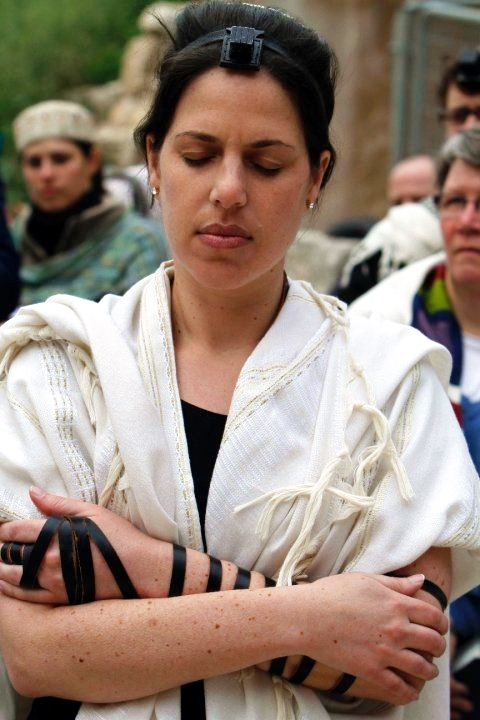 A Woman of the Wall (WOW) wears a tallit and tefillin as she prays.