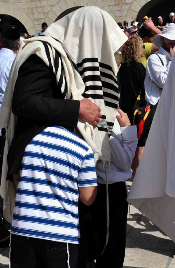 A Jewish father pulls his sons (who are each wearing a tallit katan) under his tallit gadol during the Priestly Blessing at the Western Wall in Jerusalem.