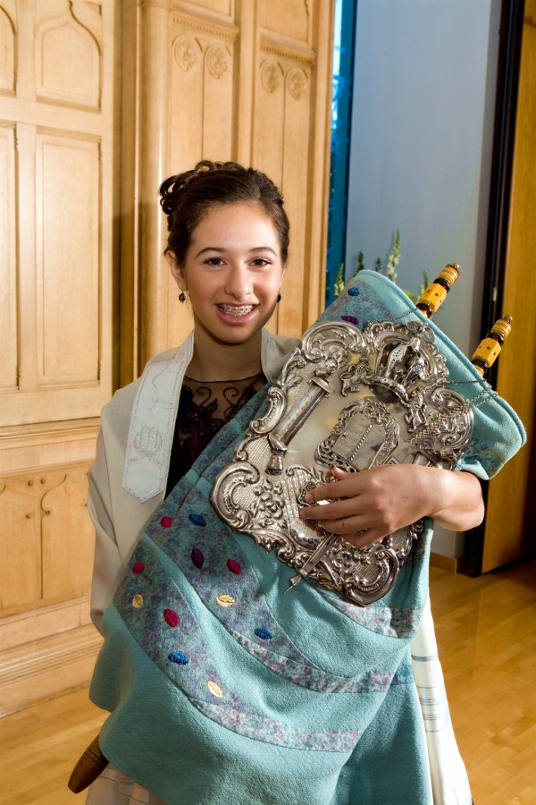 A Jewish girl holds the Torah scroll, which is covered by a Torah mantle and silver breastplate.