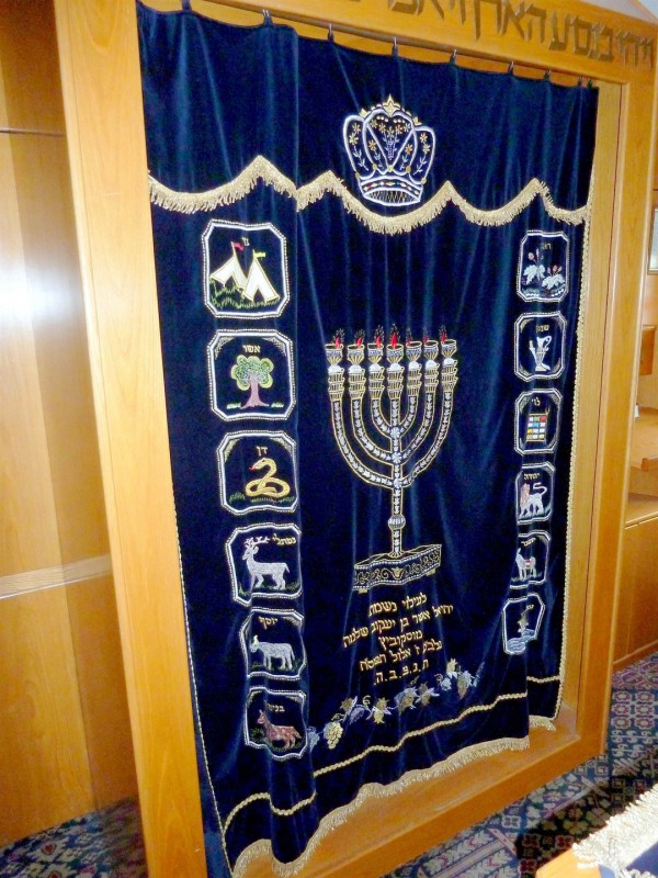 The parokhet that today covers the Torah Ark represents the Parokhet that once hung at the entrance to the Holy of Holies where the Ark of the Covenant was held. This parokhet is embroidered with symbols of the Tribes of Israel and with the Menorah.