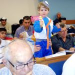 A Jewish boy spins his grogger in the synagogue as he hears Haman's name during the reading of the Megillat.