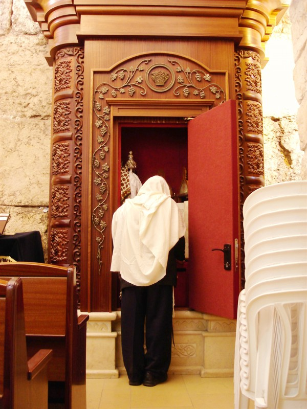 A Jewish man with his tallit (prayer shawl) draped over his head stands before an open Torah ark at the Western (Wailing) Wall.