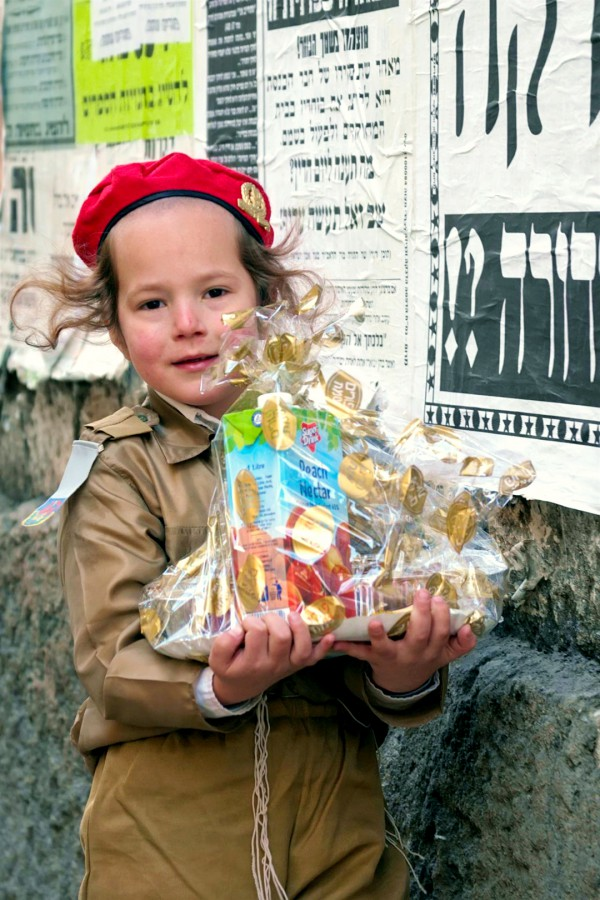 An Orthodox Israeli child dresses like an IDF soldier on Purim. He is carrying a Purim basket.