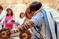 A woman reads from the Torah scroll in Jerusalem near the Western (Wailing) Wall. (Photo by Josh Evnin)