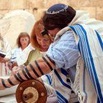 A woman reads from the Torah scroll in Jerusalem near the Western (Wailing) Wall. (Photo by Josh Evnin)
