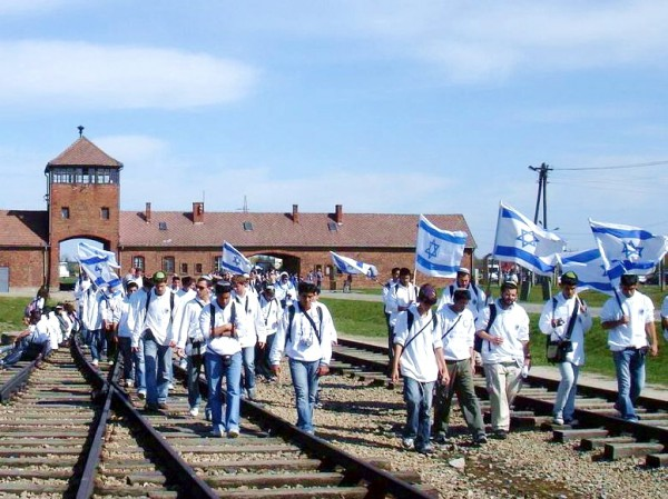 Young people raise the Israeli flag high during the March of the Living  at Auschwitz.