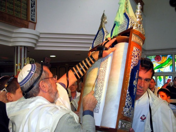 A Jewish man wearing tefillin (phylacteries) and a tallit (prayer shawl) reads from an open Torah scroll housed in an ornate Torah tik.